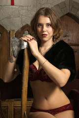 Sexy woman with axe in a medieval castle