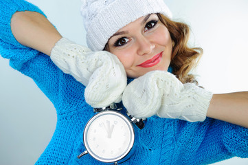 Young woman in winter clothes holding alarm clock