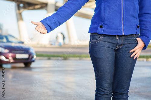 Hitching a car with thumb up on roadside