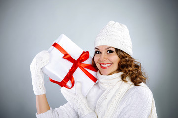 Beautiful young girl holding present box with red ribbon