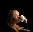 young blond hair woman with coffe  on a dark background