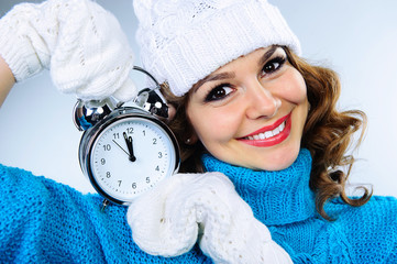 Beautiful young girl in winter clothes with alarm clock
