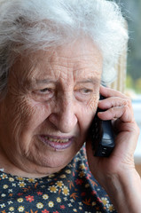 a senior woman talking on phone indoor