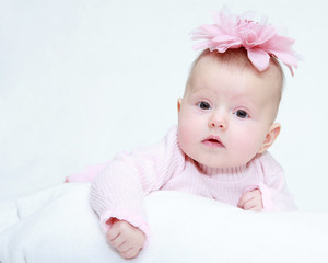 Portrait of a baby girl with a flower on her head on a white bac