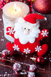 Santa Claus and Christmas candle on the old wooden background