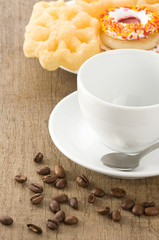 cup with coffee beans at table