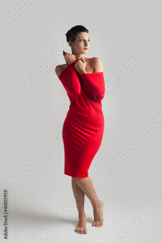 Beautiful brunette woman with red elastic cloth, studio shot.
