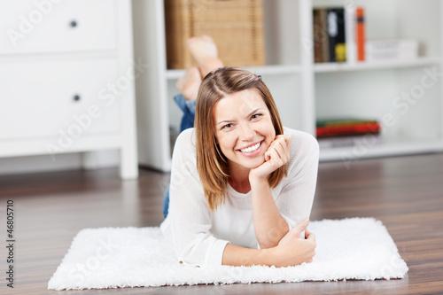 lächelnde frau liegt auf dem fußboden