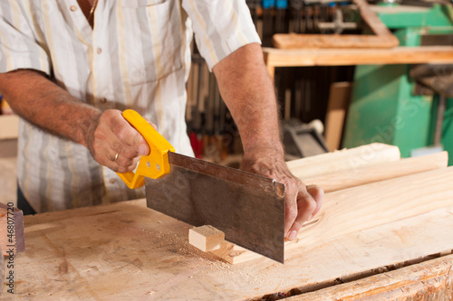 Carpenter with hand saw