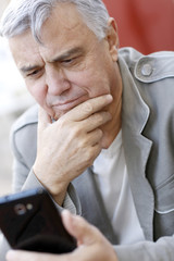 Portrait of senior man using smartphone in town