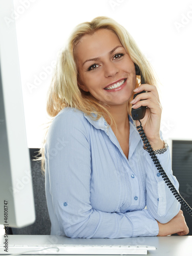 Female office assistant has a call at her work