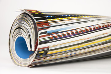 Rolled up magazines over white background