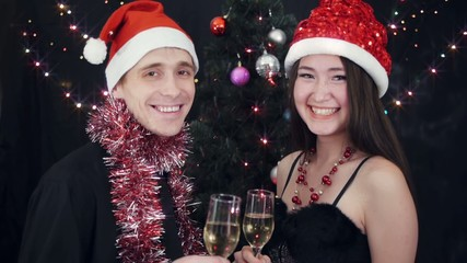 Young couple with wine glasses at christmas party