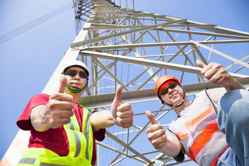 two power line workers with thumbs up