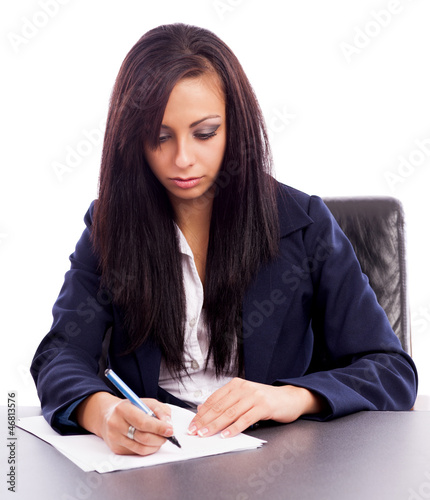 Beautiful businesswoman writing while sitting at desk isolated o