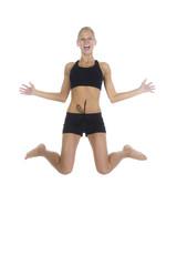 Blonde Frau springt begeistert in die Luft