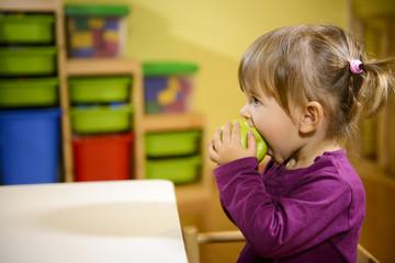female child eating green apple in kindergarten