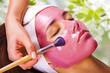 Young beautiful woman with moistening fruit facial mask at beaut
