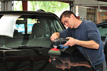 Man polishing a black car bonnet.
