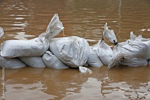 Leinwandbild Motiv sandbags for flood defense and brown water