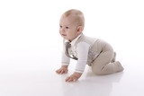 Smiling baby-boy in a romper suit crawling
