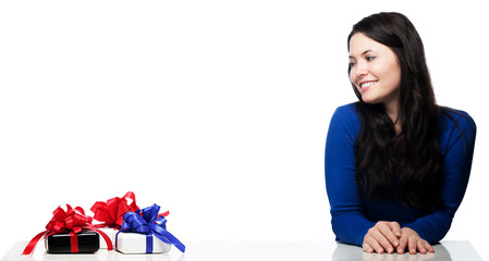Young woman at a table can not wait to to get gifts