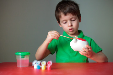 Cute little boy painting his piggy toy