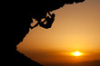 silhouette of man climbing on overhanging rock