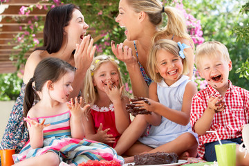 Children And Mothers Eating Jelly And Cake At Outdoor Tea Party