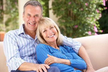 Senior Couple Relaxing On Sofa At Home