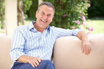 Senior Man Relaxing On Sofa At Home