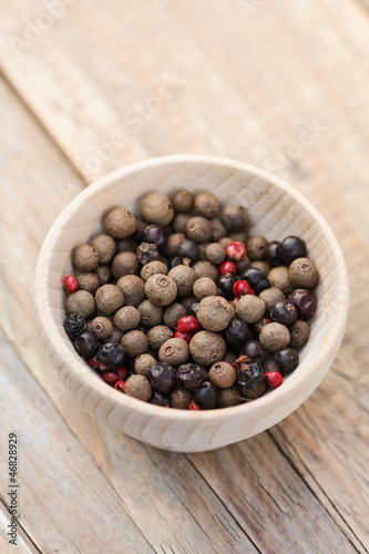 Pimento and juniper berries and pink peppercorns in a bowl