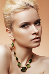 Sexy woman with beige make-up and chic jewelry