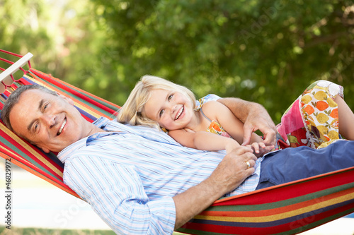 Grandfather And Granddaughter Relaxing In Hammock