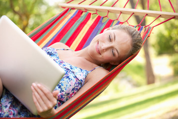 Woman Relaxing In Hammock With Laptop