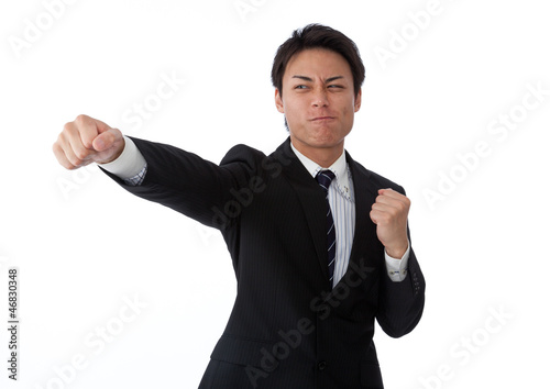 Young businessman hitting a straight punch