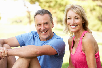Senior Couple Resting After Exercising In Park
