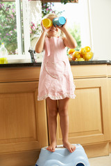 Girl Standing On Plastic Step In Kitchen Helping With Washing Up