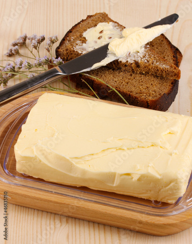 Butter on wooden holder and bread on wooden table close-up