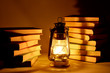 Burning kerosene lamp and books, concept magic of light