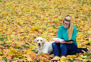 Girl with dog studying in nature