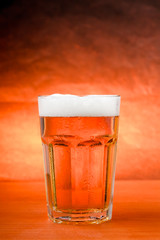 Glass of cold beer on wooden table with golden background.
