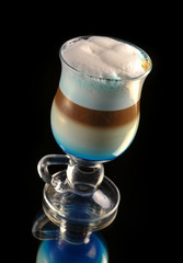cocktail with coffee and whipped milk and liqueur curacao