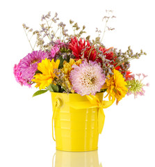 Bright yellow bucket with flowers isolated on white