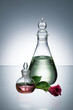 Essential oil and scent in transparent bottles and pink rose