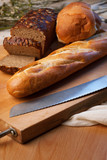 Brown bread, baguette and buns on bred-board poster