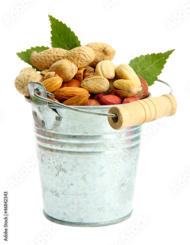 assortment of tasty nuts with leaves in pail, isolated on white