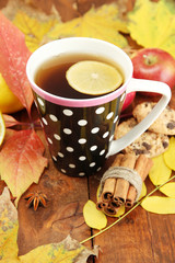 cup of hot tea and autumn leaves, on wooden background
