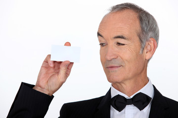 senior in a suit holding a business card