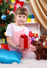 Little girl sits near a Christmas tree with gift in hand in